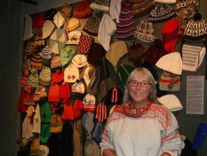 Annemor Sudnbø foran sin utstillnig med luer på Kulturtorvet.
